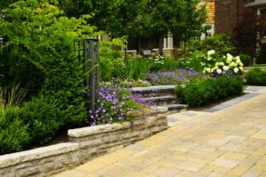 7305407 - natural stone landscaping in front of a house with lush green garden